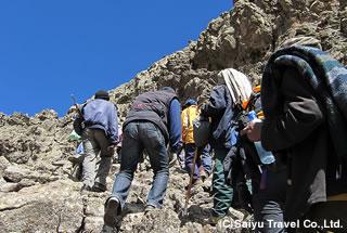 スタッフのサポートで最後の岩場を登る