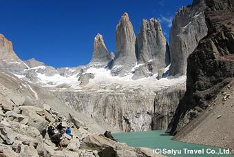 聳え立つトーレス・デル・パイネの岩峰、眼下には氷河湖