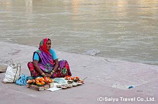 ガンジスのほとりで夕方のプージャに使う花を売る女性。